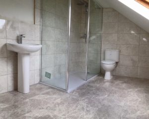 Shower, toilet and sink with floor and wall tiling